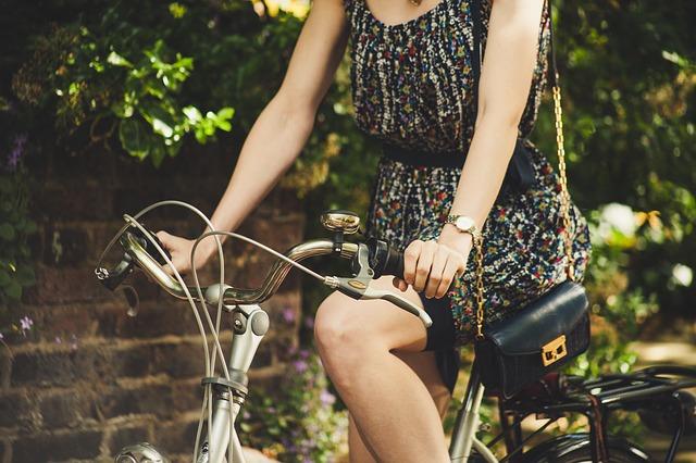 žena s kabelkou na kole